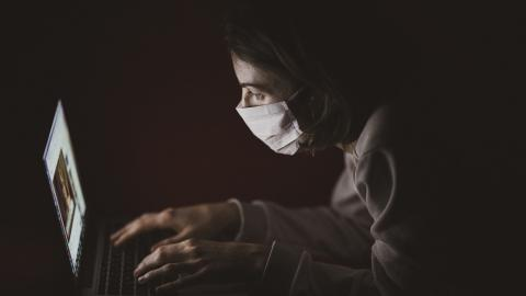 Somebody sat in the dark on a laptop wearing a face mask